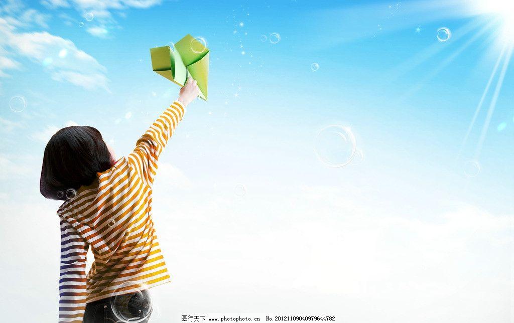 蓝天白云下拿着纸飞机的小女孩图片